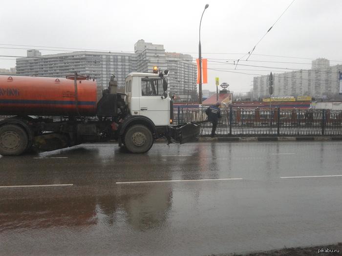 Когда в Москве еще шел дождь Фото сделано как раз в то время, на нем видно, как доблестные работники городской службы щедро поливают водой и без того мокрые загородки.
